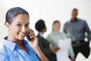 Geschäftsfrau auf Abruf mit Kollegen im Hintergrund diskutieren foto