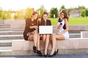 Drei erfolgreiche Geschäftsfrauen in der Stadt auf der Bank diskutierten foto