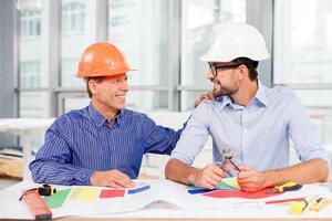 fröhliche männliche Ingenieure diskutieren den Bau foto