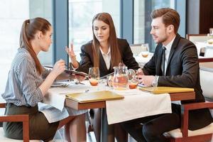 Geschäftsgespräch beim Mittagessen zwischen Kollegen foto