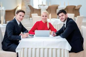 erfolgreiches Team von drei erfolgreichen Geschäftsleuten, die über Arbeit diskutieren foto