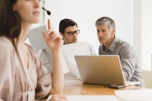 Geschäftsfrau, die ein Headset mit zwei Geschäftsleuten trägt, die diskutieren