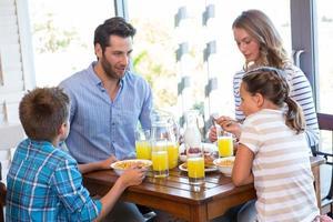 glückliche Familie beim gemeinsamen Frühstück foto