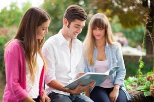 Freunde, die zusammen ein Notizbuch lesen foto