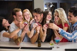 glückliche Freunde, die zusammen etwas trinken foto