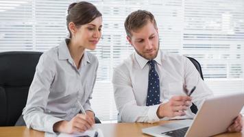 Geschäftsleute, die mit Laptop zusammenarbeiten