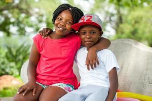 afrikanische Kinder sitzen zusammen auf Bank.