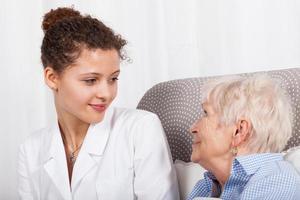 reife Dame und Krankenschwester lächeln zusammen