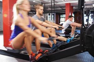 Gymnastikklasse, die gemeinsam an Rudergeräten trainiert foto