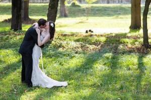 elegante Braut und Bräutigam posieren zusammen im Freien foto