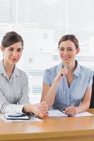 lächelnde Geschäftsfrauen, die zusammenarbeiten und Kamera betrachten
