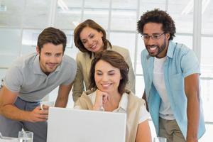 Geschäftsleute, die Laptop zusammen am Schreibtisch verwenden foto