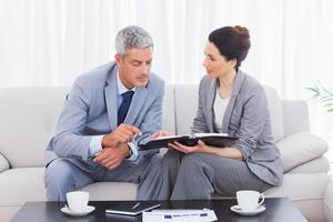 ernsthafte Geschäftsleute, die zusammen auf dem Sofa arbeiten und reden foto