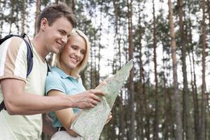 glückliche junge Rucksacktouristen, die Karte im Wald betrachten