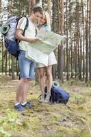 in voller Länge des jungen Wanderpaares, das Karte im Wald liest