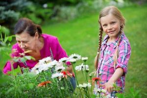 Mädchen und Oma arbeiten zusammen im Garten foto