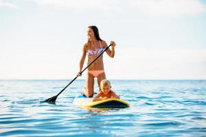 Mutter und Sohn stehen zusammen auf und paddeln foto