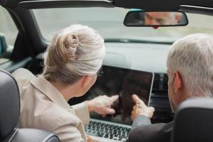 Geschäftsleute, die zusammen auf Laptop im noblen Cabriolet arbeiten foto