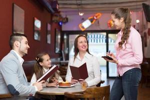 Kellnerin und glückliche Familie foto