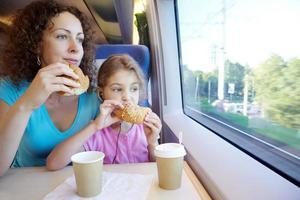Mutter und Tochter essen in der Nähe des Fensters foto