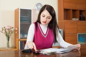 ernsthafte Frau, die das Familienbudget berechnet foto