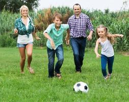 fröhliche Familie läuft mit Ball foto