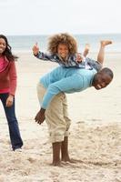 glückliche Familie, die am Strand spielt foto