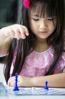 kleines asiatisches Kind, das Schach spielt foto