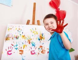 Kind macht Handabdruck mit Farbe.