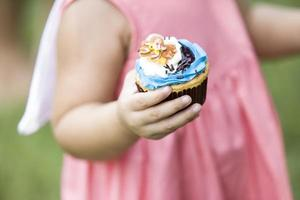 Kind hält eine Fantasie Tasse Kuchen foto