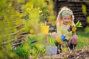 Kindermädchen, das Blumen im Frühlingsgarten pflanzt foto