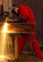 Schweißer in roten Overalls schneidet Metall.