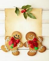 lächelnde Lebkuchenmänner auf einem Stück Pergament mit Stechpalme