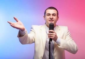 Mann im weißen Anzug mit Mikrofon. lebhafte Gefühle. farbiger Rücken foto