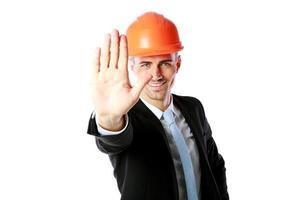 Geschäftsmann im Helm zeigt Stoppgeste