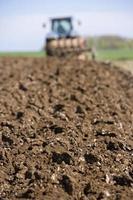 Nahaufnahme des gepflügten Feldes mit Traktor und Pflug foto