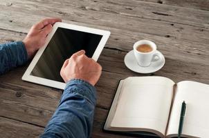 Die Hand des Mannes drückt auf den Tablet-Computer mit leerem Bildschirm foto