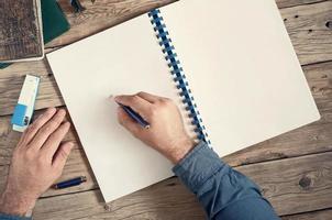 Die Männer schreiben in ein offenes Notizbuch mit leeren Seiten foto