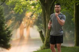 Mannläufer, der im Freien Training in einem Park joggt foto