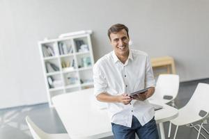 junger Mann mit Tablette im Büro foto