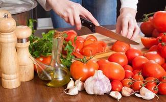 weibliche Hände, die Tomaten schneiden foto