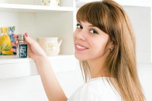 junge Frau, die einen Salzstreuer nimmt foto