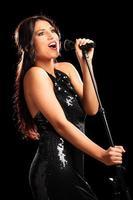 schöne Sängerin singt auf einem Mikrofon foto
