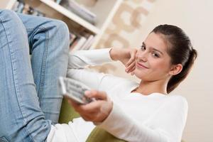 Studenten - lächelnder weiblicher Teenager, der fernsieht