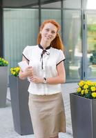 Studentin, die draußen mit Buch geht foto