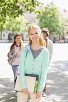 Porträt der jungen Studentin mit Freunden foto