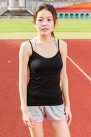 weiblicher Athlet, der entspannt auf Sportplatz steht foto