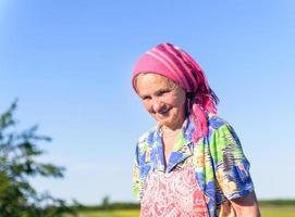lächelnde ältere Bäuerin auf den grünen Feldern foto