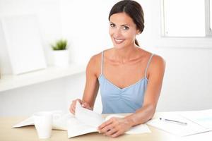 freundliche brünette Frau sitzt und liest Bücher foto