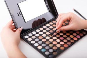 weibliche Hand, die Make-up-Pinsel und Farben hält foto
